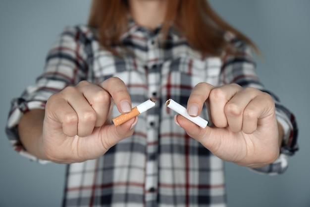 Close de uma mulher quebrando o cigarro nas mãos