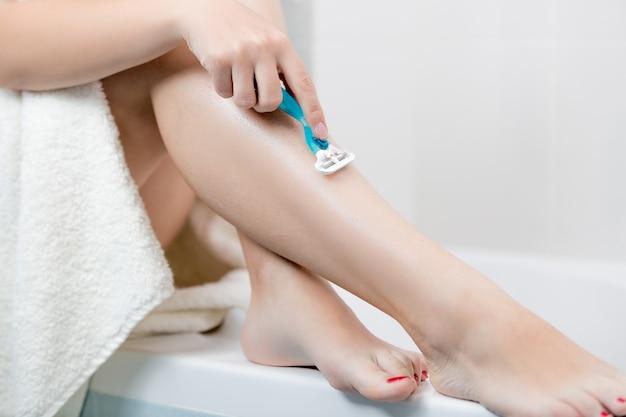 Close de uma mulher raspando as pernas depois de tomar banho