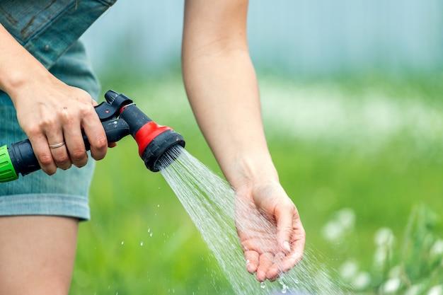 Close de uma mulher regando as plantas no jardim