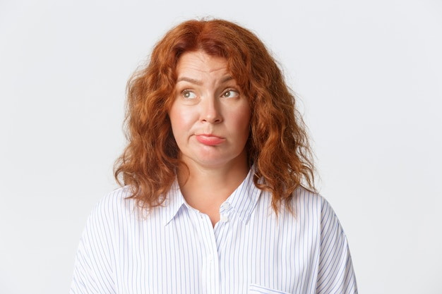 Close de uma mulher ruiva de meia-idade indecisa e hesitante pensando nas opções
