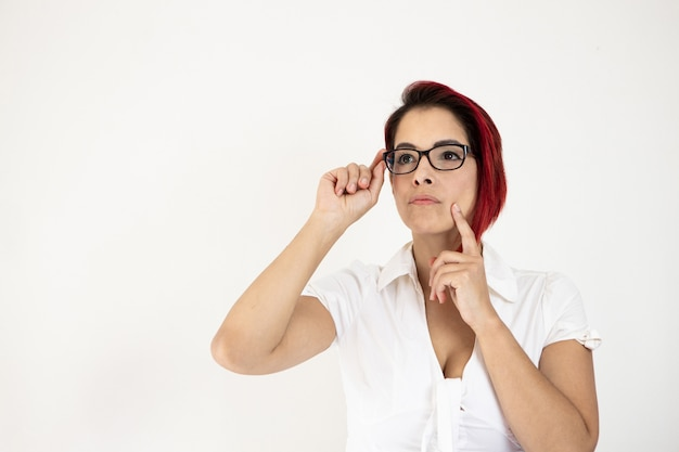 Close de uma mulher ruiva de meia-idade, isolada em uma parede branca