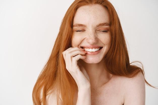 Close de uma mulher ruiva feliz com a pele pálida, sem maquiagem e com um sorriso perfeito, rindo e parecendo alegre, em pé nua sobre uma parede branca
