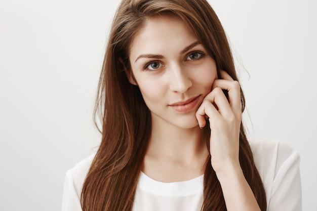 Close de uma mulher sedutora e carinhosa olhando para a frente, coquete, sorrindo sensual