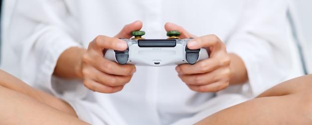 Close de uma mulher segurando o controlador de jogo enquanto jogava, sentado em uma cama aconchegante branca em casa