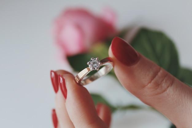 Close de uma mulher segurando um anel de diamante de ouro com uma rosa rosa