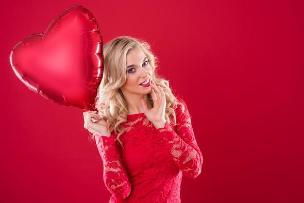 Close de uma mulher segurando um balão vermelho Foto gratuita