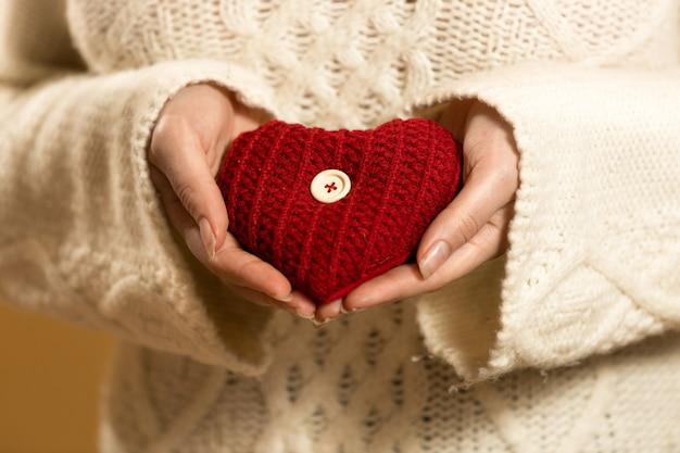 Close de uma mulher segurando um coração vermelho nas mãos