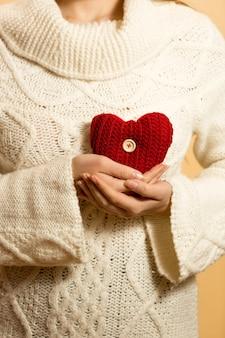 Close de uma mulher segurando um coração vermelho no peito