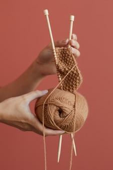Close de uma mulher segurando um fio e agulhas e tricotando um lenço quente na parede rosa