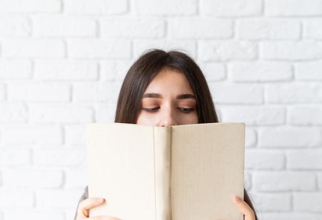 Close de uma mulher segurando um livro aberto na frente do rosto