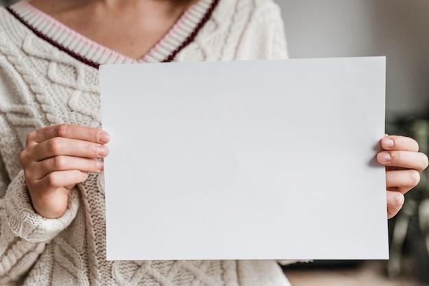 Close de uma mulher segurando um papel em branco