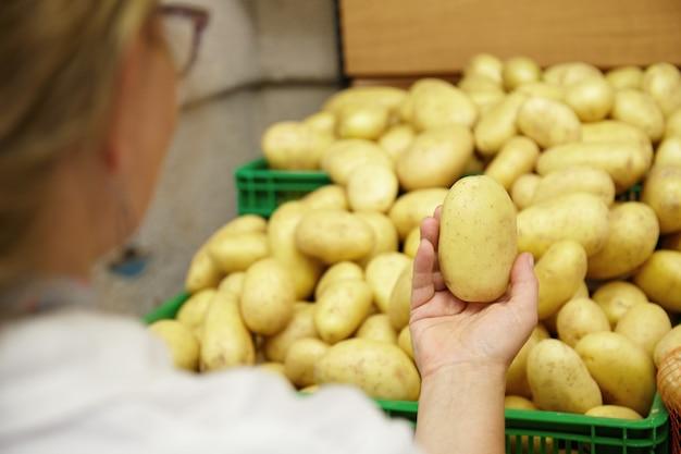 Close de uma mulher segurando uma batata na mão