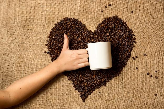 Close de uma mulher segurando uma caneca contra um coração feito de grãos de café