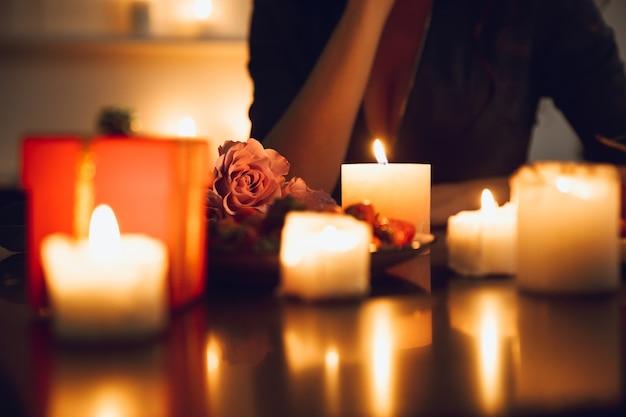 Close de uma mulher sentada à mesa à luz de velas