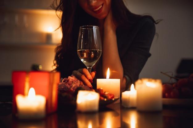 Close de uma mulher sentada com uma taça de vinho à mesa à luz de velas