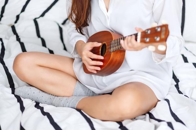 Close de uma mulher sentada e tocando cavaquinho em uma cama branca e aconchegante em casa