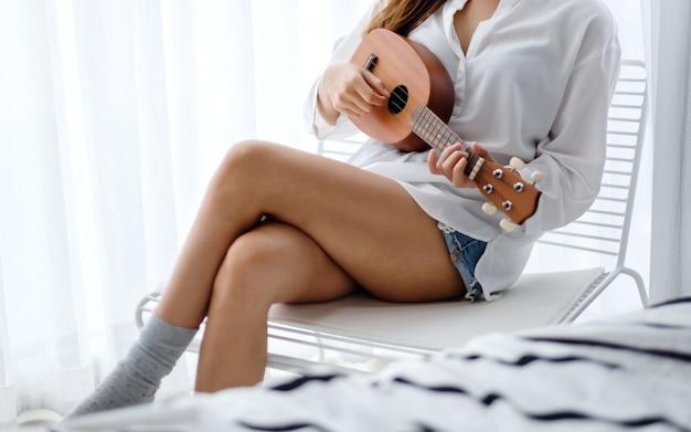 Close de uma mulher sentada e tocando cavaquinho no quarto