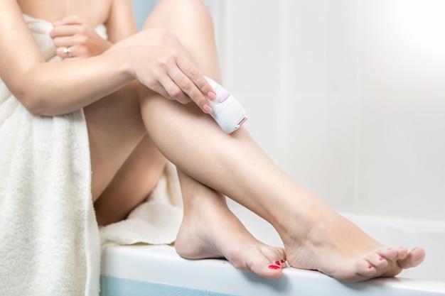 Close de uma mulher sentada na banheira removendo pelos nas pernas