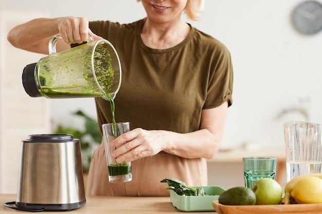 Close de uma mulher servindo suco do liquidificador no copo e bebendo pela manhã