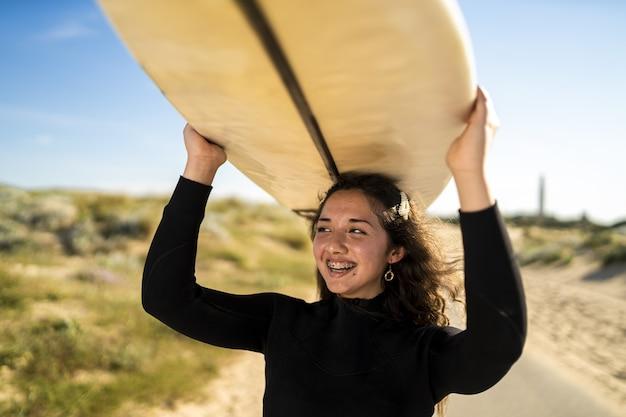Close de uma mulher sorridente carregando uma prancha de surf acima da cabeça