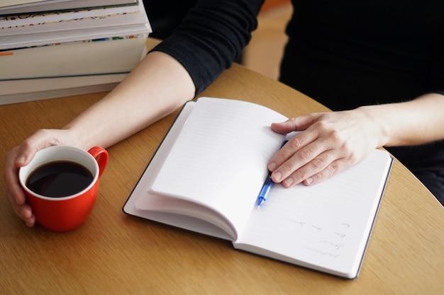 Close de uma mulher trabalhando ou estudando em casa com um café vermelho na mão