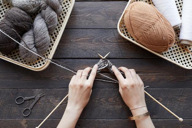 Close de uma mulher tricotando um cachecol de diferentes fios com agulhas de tricô na mesa de madeira