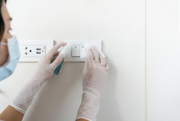 Close de uma mulher usando máscara e luvas, desinfetando os interruptores