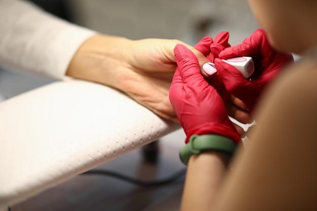 Close de uma mulher usando meios de proteção manicure cobrindo as unhas