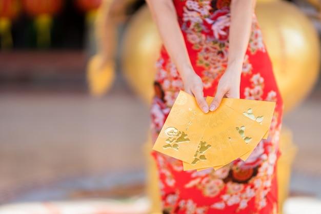 Close de uma mulher vestindo um cheongsam chinês tradicional vermelho, segurando envelopes amarelos para o festival do ano novo chinês no santuário chinês