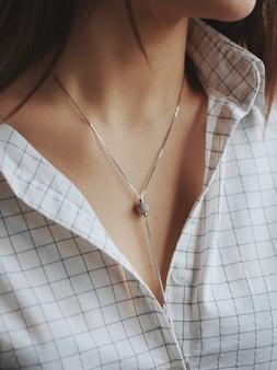 Close de uma mulher vestindo uma camisa branca e um delicado colar de prata
