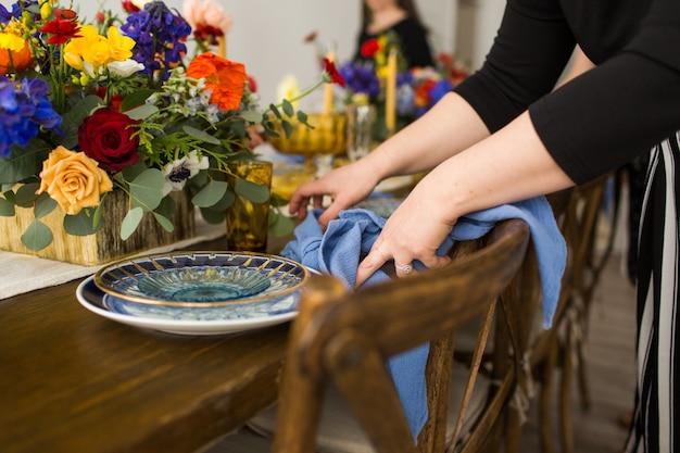 Close de uma mulher vestindo uma camisa preta dobrando os guardanapos azuis para a mesa