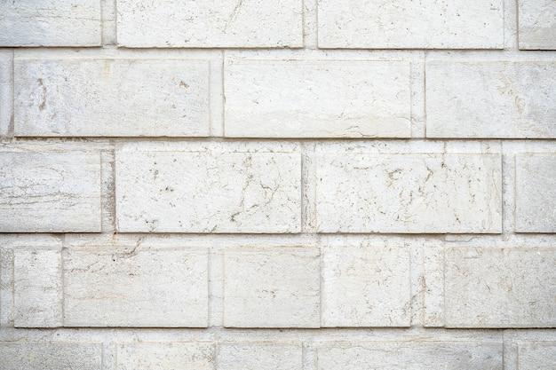 Close de uma parede feita de pedras retangulares brancas com fundo