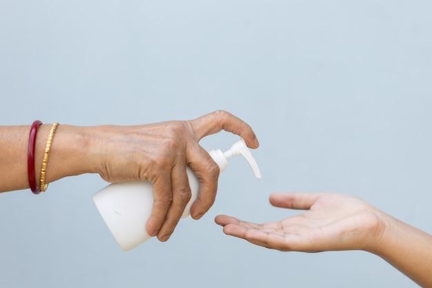 Close de uma pessoa derramando sabonete líquido na mão de outra pessoa