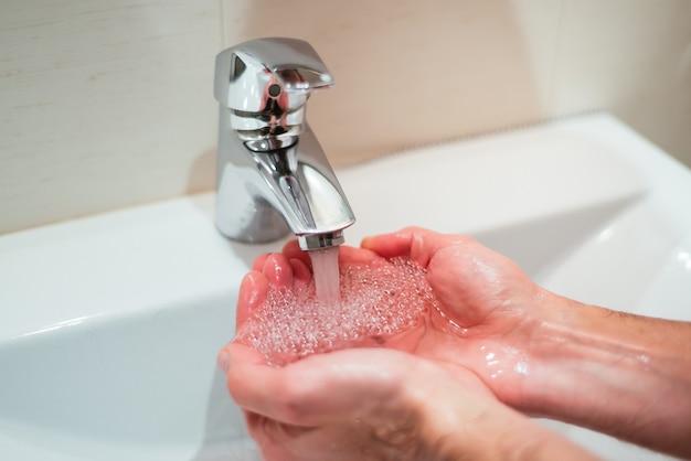 Close de uma pessoa lavando as mãos na pia