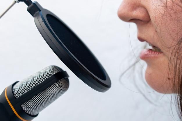 Close de uma pessoa pegando um microfone preto e cinza capturado em um fundo branco