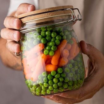 Close de uma pessoa segurando ervilhas e cenouras em frasco de vidro