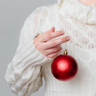 Close de uma pessoa segurando uma decoração de natal