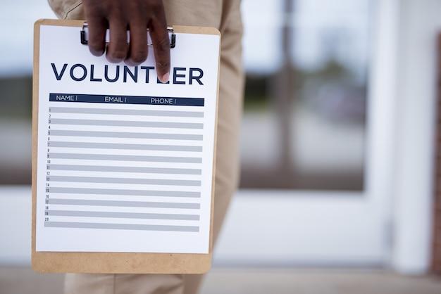 Close de uma pessoa segurando uma folha de inscrição de voluntário