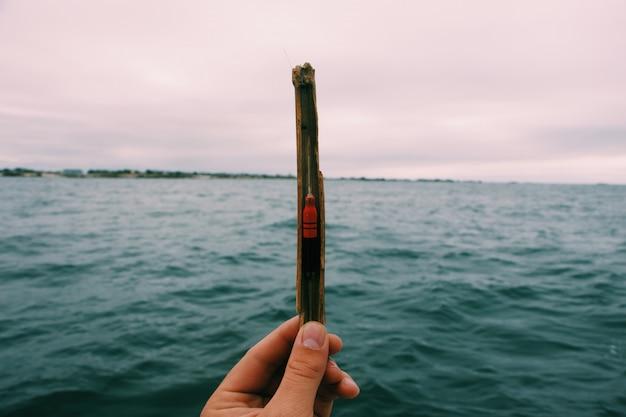 Close de uma pessoa segurando uma isca de pesca com um mar turva e um céu nublado