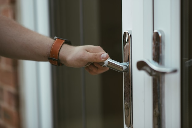 Close de uma pessoa segurando uma maçaneta e abrindo a porta