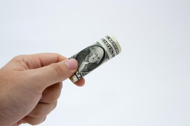 Close de uma pessoa segurando uma nota de dólar dobrada em uma parede cinza