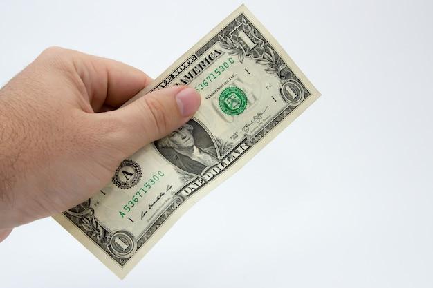Close de uma pessoa segurando uma nota de um dólar