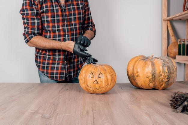 Close de uma pessoa usando luvas de látex e se preparando para esculpir uma abóbora no halloween