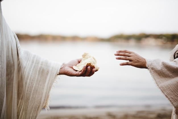 Close de uma pessoa vestindo um manto bíblico dando pão para outra pessoa