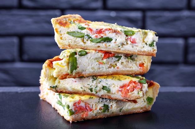 Close de uma pilha de fatias de quiche com recheio de queijo de aspargos de salmão em uma mesa de concreto com uma parede de tijolos vista horizontal de cima
