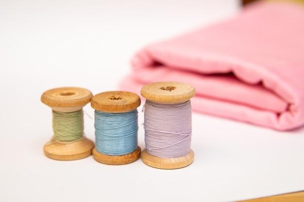 Close de uma pilha de tecido rosa dobrado, tesouras de costura e carretéis de linha