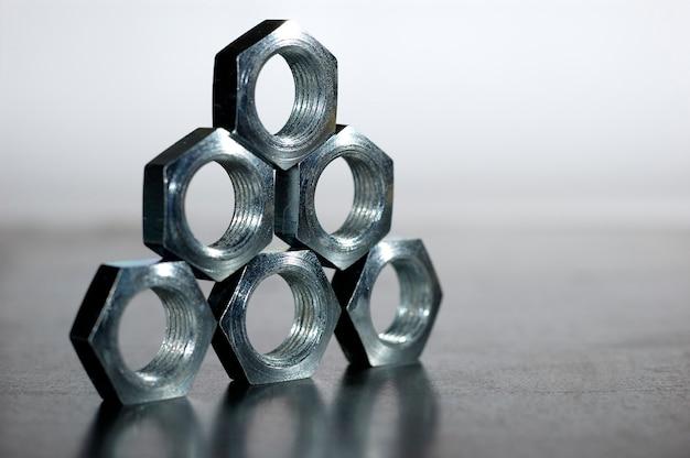 Close de uma pirâmide de cinco porcas de metal cromado em forma de favos de mel lado a lado