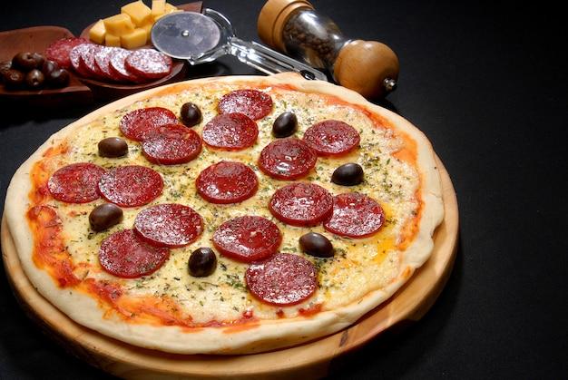 Close de uma pizza de calabresa coberta com azeitonas assadas e outros ingredientes de pizza ao lado