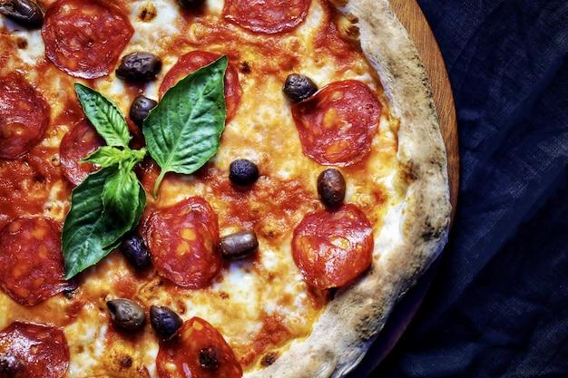 Close de uma pizza de calabresa em uma placa de madeira sob as luzes