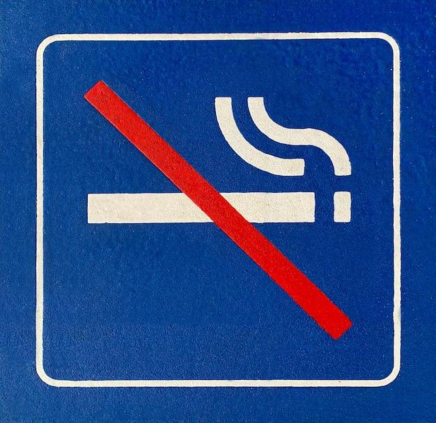 Close de uma placa azul de proibido fumar